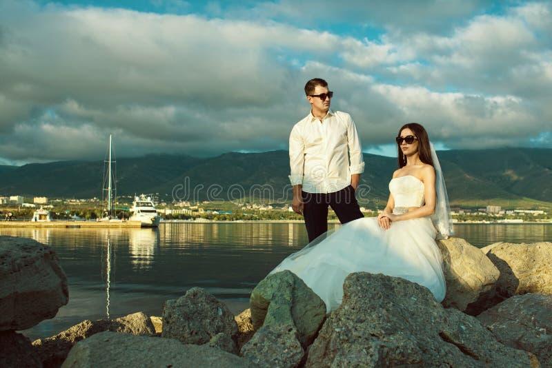 Portret van jong enkel echtpaar in huwelijkstoga's en modieuze zonnebril op de rots bij de kust stock foto's