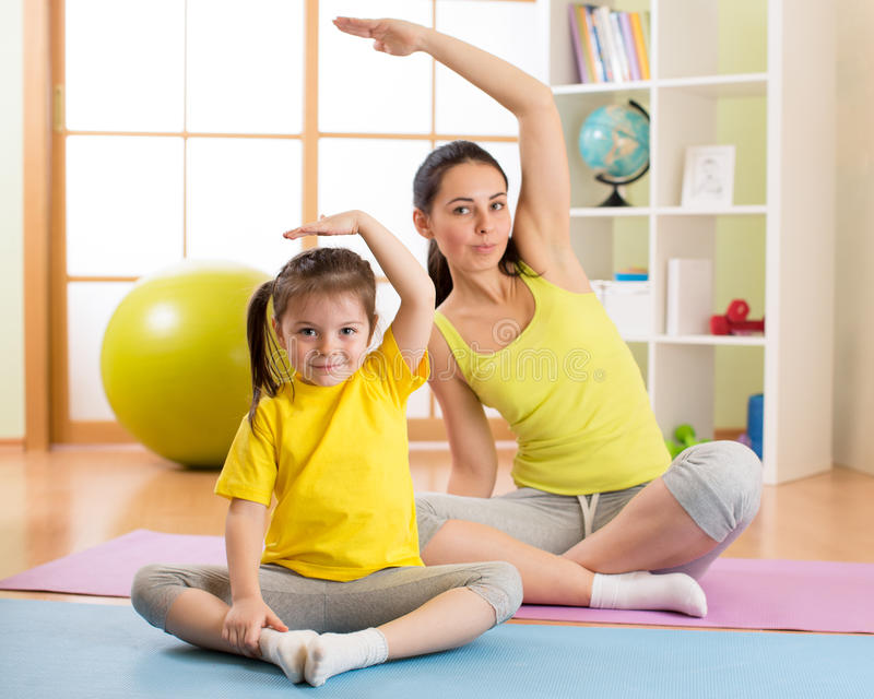Portret van jong geitje en moeder die lichaamsbeweging thuis doen royalty-vrije stock afbeelding