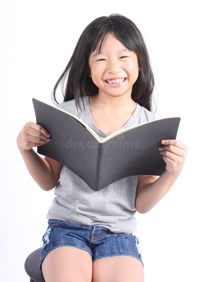 Portret van jong gelukkig meisje met boek stock foto