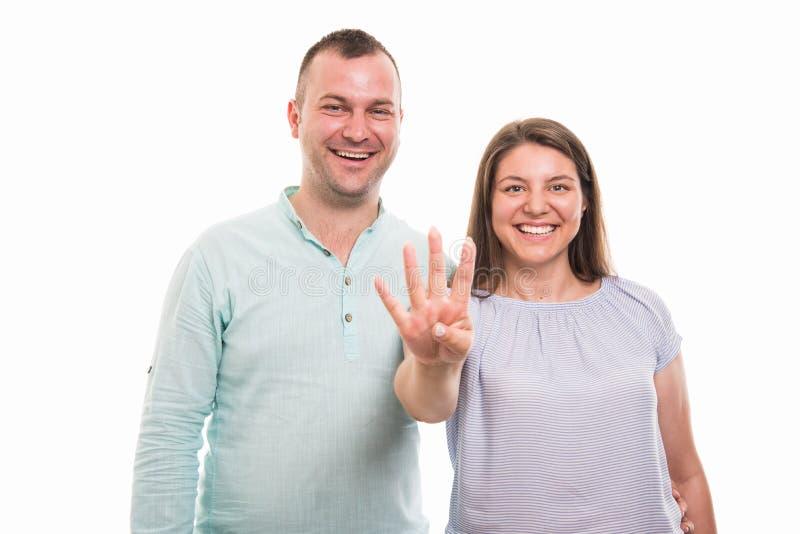 Portret van jong gelukkig paar die nummer vier met vingers tonen stock foto