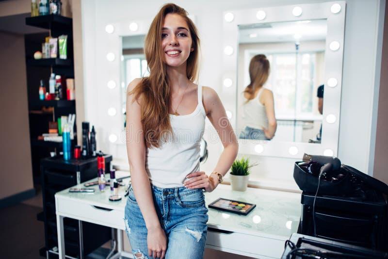 Portret van jong het glimlachen vrouwelijk model met lang eerlijk haar die vrijetijdskleding dragen die zich in samenstellingsstu stock foto