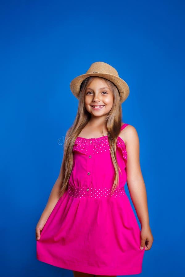 Portret van jong leuk meisje in roze kleding en hoed op blauwe achtergrond De zomervakantie en reisconcept royalty-vrije stock afbeeldingen