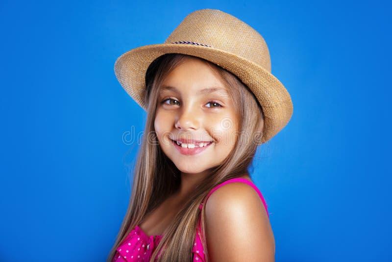Portret van jong leuk meisje in roze kleding en hoed op blauwe achtergrond De zomervakantie en reisconcept stock afbeeldingen