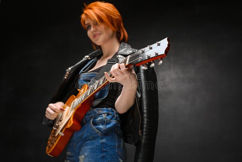 Portret van jong meisje met gitaar over zwarte achtergrond royalty-vrije stock afbeeldingen