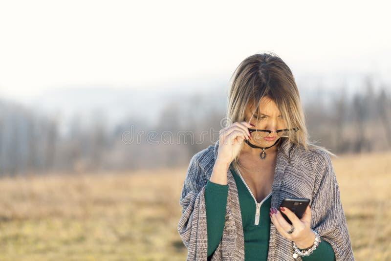 Portret van jong meisje met telefoon en glazen stock foto