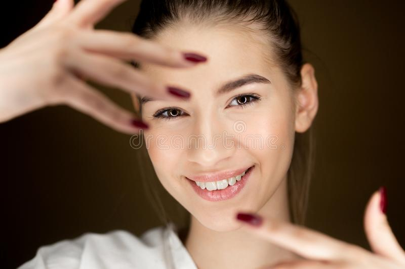 Portret van jong mooi bruin-haired meisje die met natuurlijke make-up haar vingers voor haar gezicht houden stock foto's