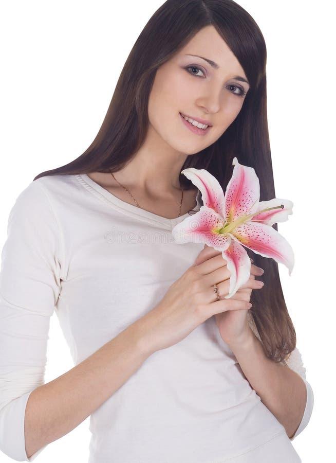 Portret van jong mooi brunette met bloem in handen stock afbeelding