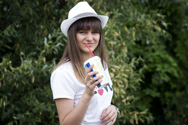 Portret van jong mooi glimlachend meisje in hoed met cocktailglas met stro in hand in openlucht De stemming van de zomer royalty-vrije stock foto's