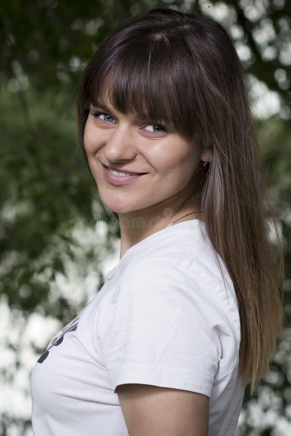 Portret van jong mooi leuk glimlachend meisje tegen achtergrond van groene de zomeraard royalty-vrije stock afbeeldingen