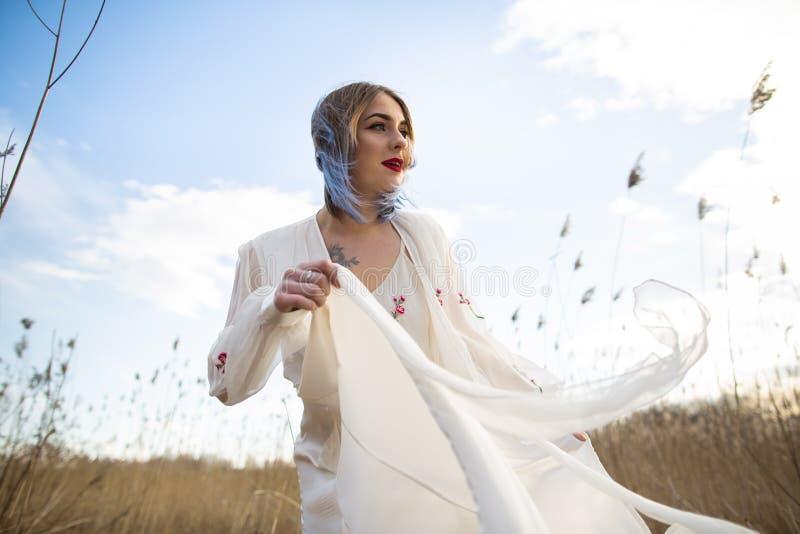 Portret van jong mooi meisje in de witte kleding op tarwegebied, onbezorgd lopen, Het genieten van de van mooie zonnige dag royalty-vrije stock afbeelding