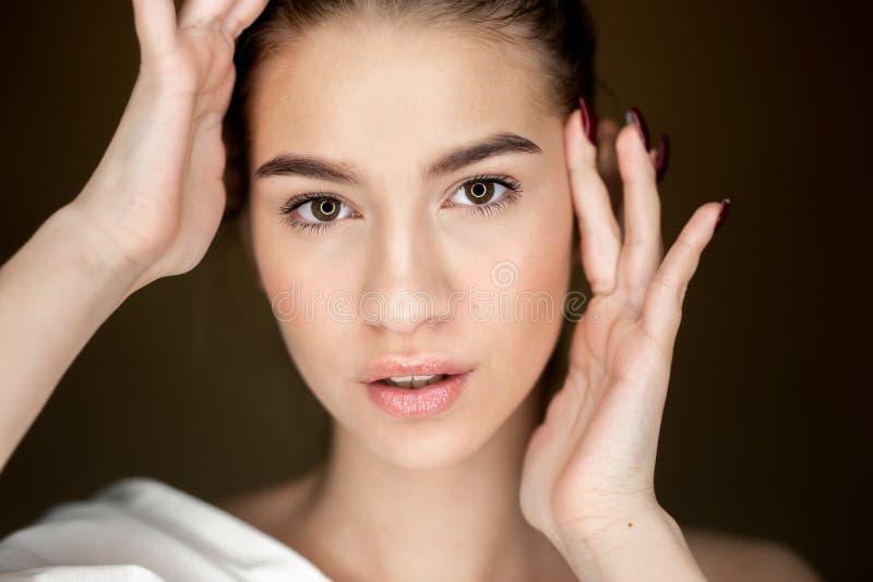 Portret van jong mooi meisje die met natuurlijke make-up haar handen op haar hoofd houden stock fotografie