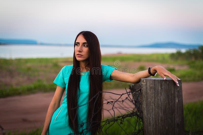 Portret van jong mooi meisje in een turkooise kleding dichtbij prikkeldraad in de zomer openlucht royalty-vrije stock foto