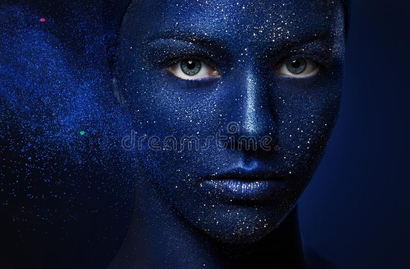 Portret van jong mooi meisje het gezicht met blauwe verf wordt geschilderd die en schittert stock foto