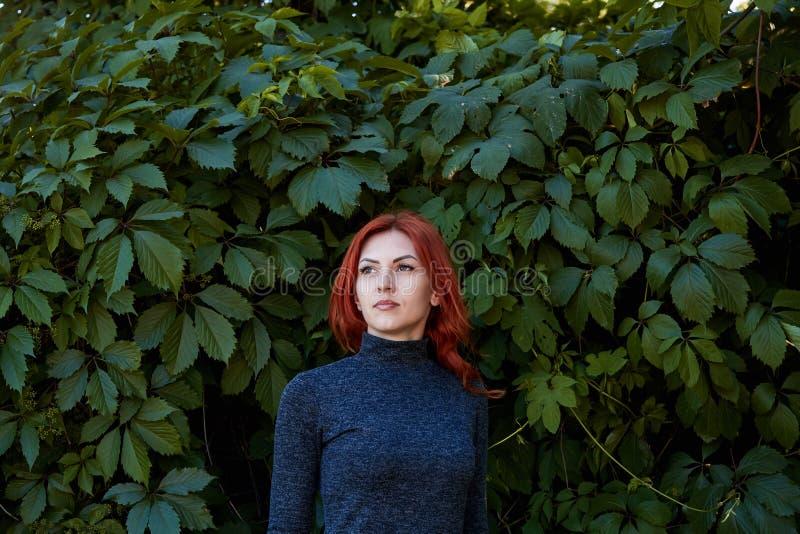 Portret van jong mooi meisje met mooie verschijning De roodharige vrouw met een mooi gezicht stelt in een nauwsluitende kleding A stock afbeeldingen
