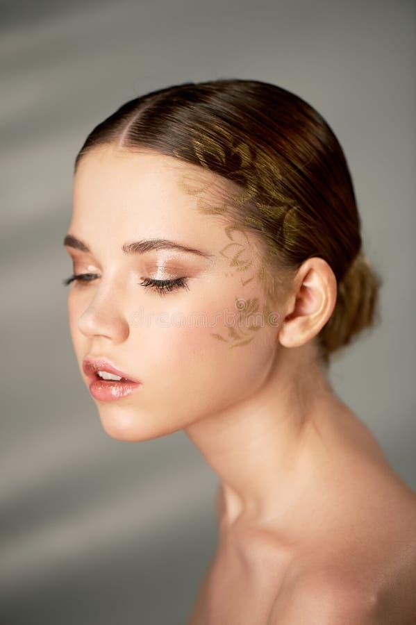 Download Portret Van Jong Mooi Meisje In Studio, Met Professionele Make-up Schoonheid Het Schieten Voor Het Bespoten Goud Van Het Gezichts Stock Afbeelding - Afbeelding bestaande uit haar, gezichts: 114227591