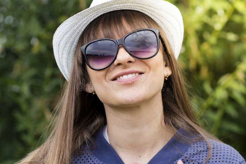 Portret van jong mooi meisje in zonnebril en hoed in goede stemming die tegen groen de zomerpark glimlachen stock foto's