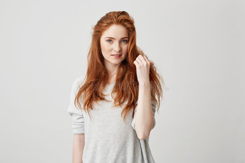 Portret van jong mooi roodharigemeisje die met sproeten camera bekijken die wat betreft haar over witte achtergrond glimlachen royalty-vrije stock fotografie