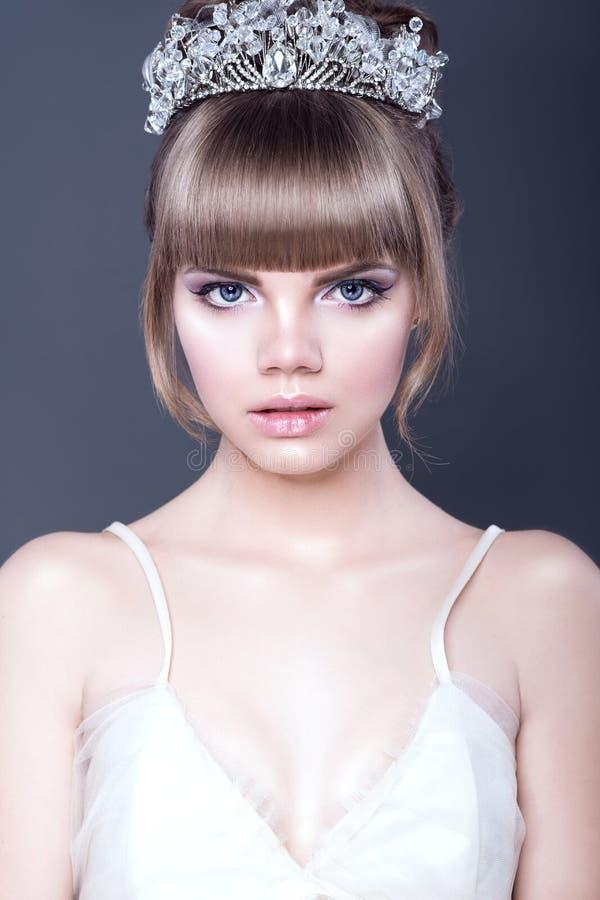 Portret van jong mooi tienermeisje met expressieve blauwe ogen en volledige gescheiden lippen die kristalkroon dragen die recht k royalty-vrije stock afbeelding