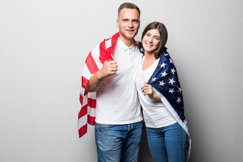 Portret van jong paar dat in Amerikaanse vlag wordt verpakt die op witte achtergrond wordt geïsoleerd stock foto