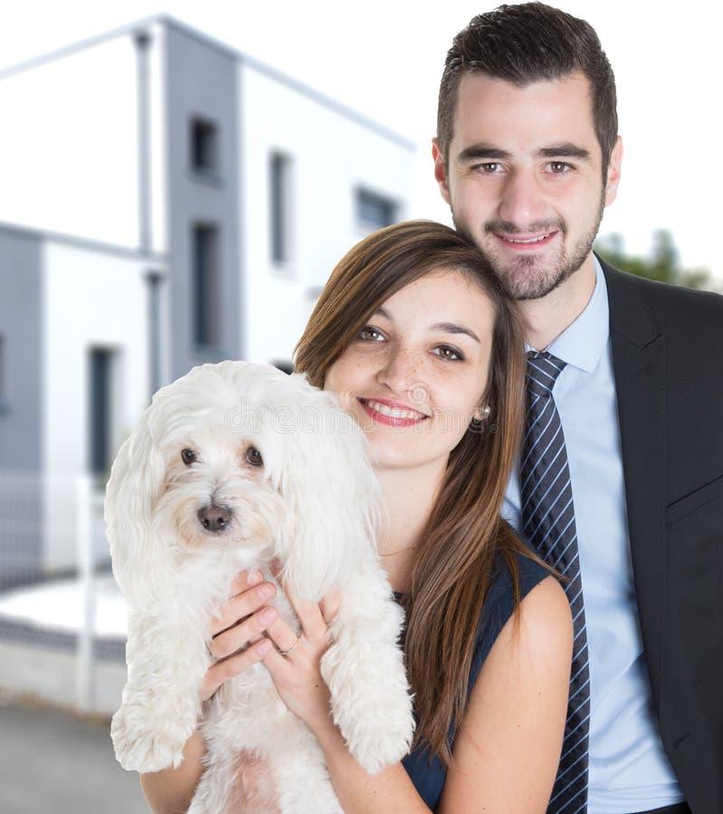 Portret van jong Paar met witte hond die over het Achter moderne huis van de het architectuurontwerpstijl van de Yardomheining ki royalty-vrije stock afbeeldingen