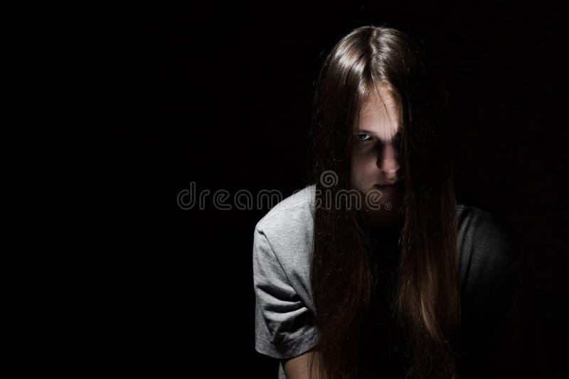 Portret van jong tiener donkerbruin meisje met lang haar in de Gotische stijl op een zwarte achtergrond stock foto's