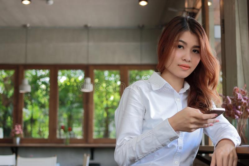 Portret van jonge aantrekkelijke Aziatische bedrijfsvrouw die mobiele slimme telefoon houden en camera in koffiewinkel bekijken m stock foto