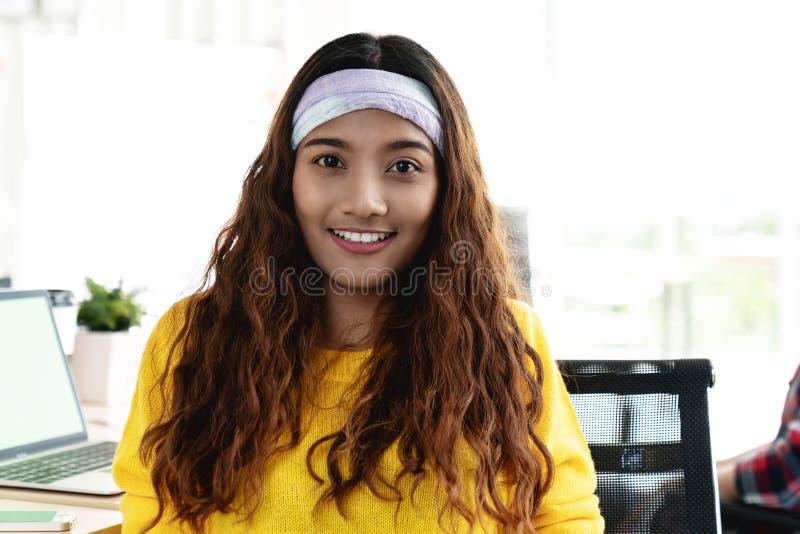 Portret van jonge aantrekkelijke Aziatische creatieve vrouw of ontwerper die en camera glimlachen bekijken royalty-vrije stock foto