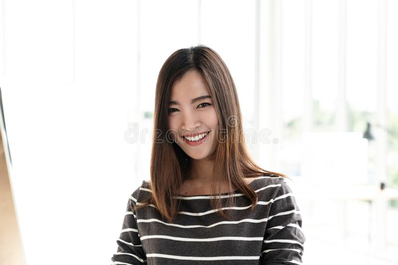 Portret van jonge aantrekkelijke Aziatische creatieve vrouw of ontwerper die en camera in modern bureau glimlachen bekijken die z royalty-vrije stock afbeeldingen