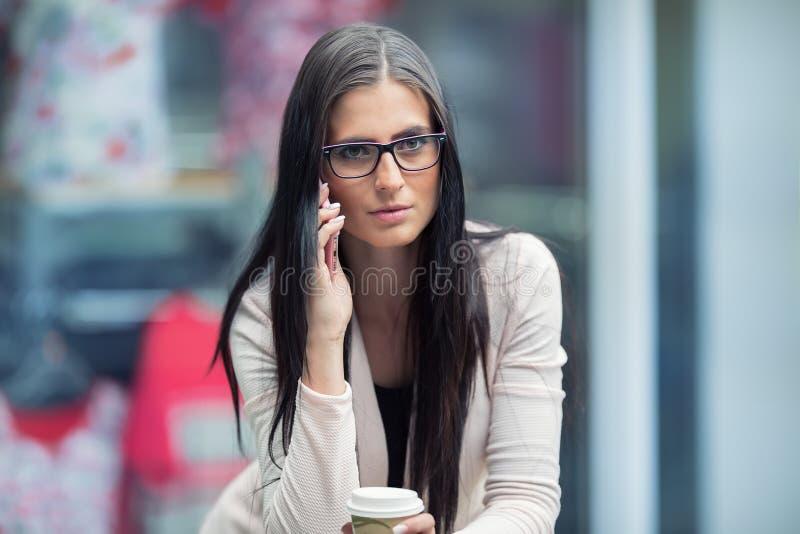 Portret van jonge aantrekkelijke bedrijfsvrouw status in het winkelcomplex met koffie en het gebruiken van haar celtelefoon grafi royalty-vrije stock foto's