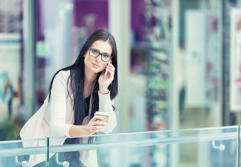 Portret van jonge aantrekkelijke bedrijfsvrouw status in het winkelcomplex met koffie en het gebruiken van haar celtelefoon grafi stock foto's