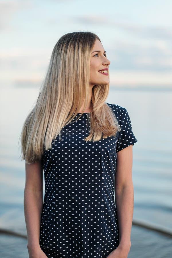 Portret van jonge aantrekkelijke blonde vrouw, in een blauwe kleding in openlucht, handen op gezicht royalty-vrije stock fotografie