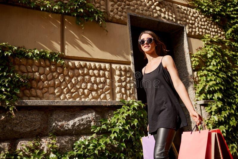 Portret van jonge aantrekkelijke donker-haired Kaukasische vrouw die in tan glazen en zwarte modieuze uitrusting onderaan straat  royalty-vrije stock foto's