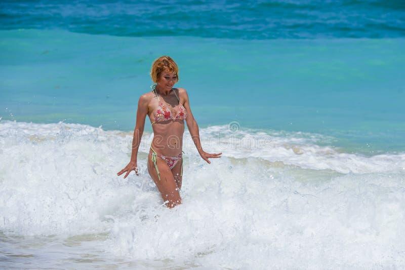 Portret van jonge aantrekkelijke en gelukkige vrouw in bikini het stellen bij verbazend mooi woestijnstrand met grote golven die  stock afbeeldingen
