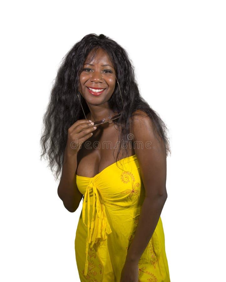 Portret van jonge aantrekkelijke en gelukkige zwarte Afrikaanse Amerikaanse vrouw in elegante gele kleding die het koele vrolijk  stock foto