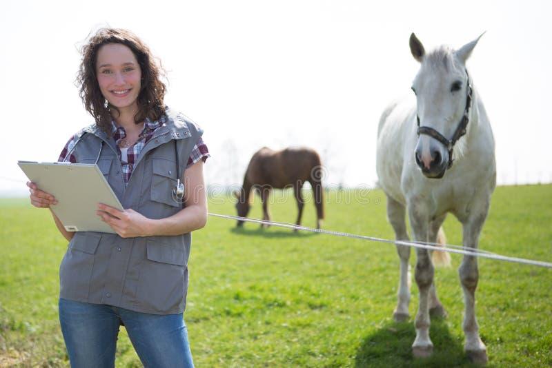 Portret van jonge aantrekkelijke veterinair op gebieden met paard stock foto's