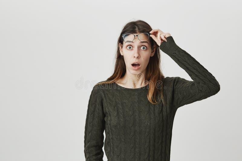 Portret van jonge aantrekkelijke vrouw met geopende mond en verrast, geschokte uitdrukking, die glazen in donkergroen steunen stock foto's