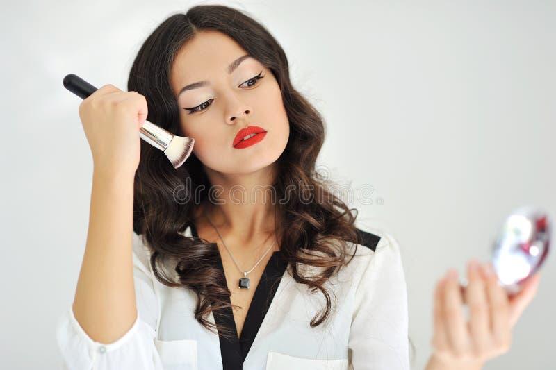 Portret van jonge aantrekkelijke vrouw met make-upborstel over wit stock fotografie