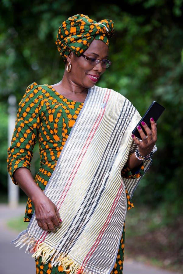 Portret van jonge Afrikaanse vrouw met mobiele telefoon, het glimlachen stock foto