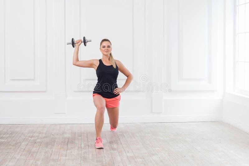 Portret van jonge atletische mooie bodybuildervrouw in roze borrels en zwarte bovenkant die hurkzit doen en bij de gymnastiek uit royalty-vrije stock foto