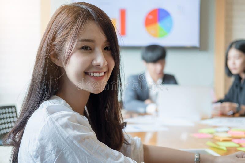 Portret van jonge Aziatische vrouw in bureau met medewerkers die I spreken stock afbeelding
