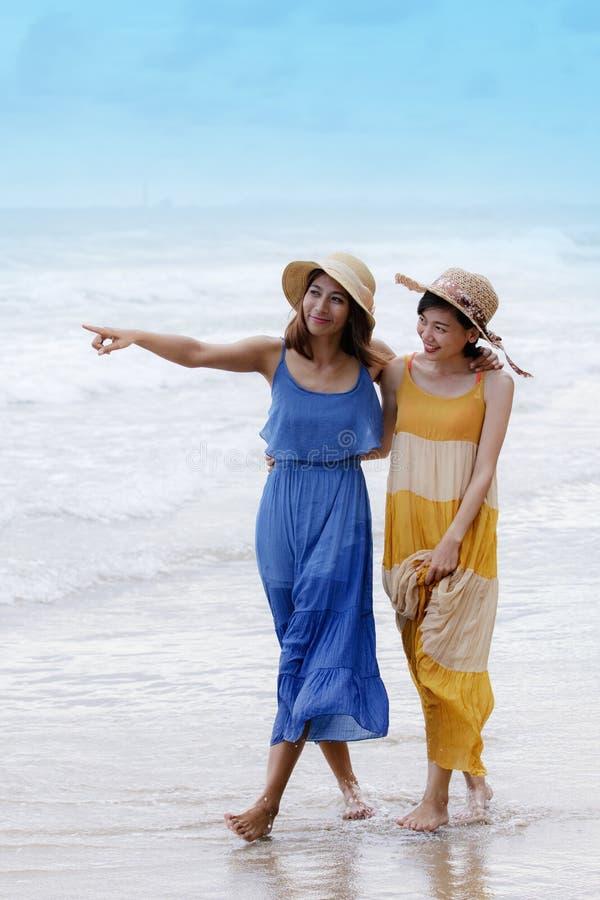 Portret van jonge Aziatische vrouw die met gelukemotie mooie kleding dragen die op overzees strand en het lachen blij gebruik lop stock foto's