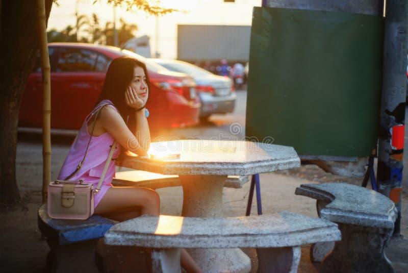 Portret van jonge Aziatische vrouw met weinig zakzitting op marmeren stoel voor het wachten van iemand op zonsondergangogenblik,  royalty-vrije stock foto