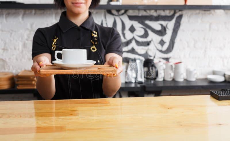 Portret van jonge barista bij de teller van de koffiewinkel stock afbeeldingen