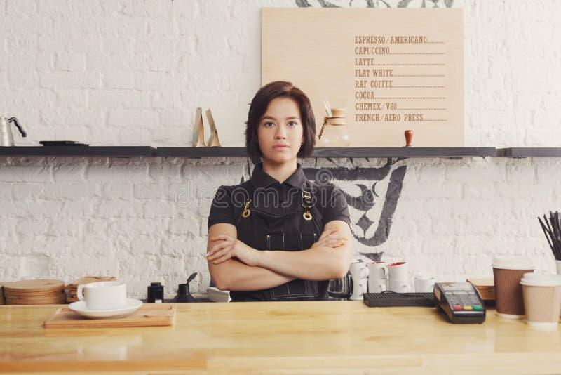 Portret van jonge barman bij de teller van de koffiewinkel stock foto