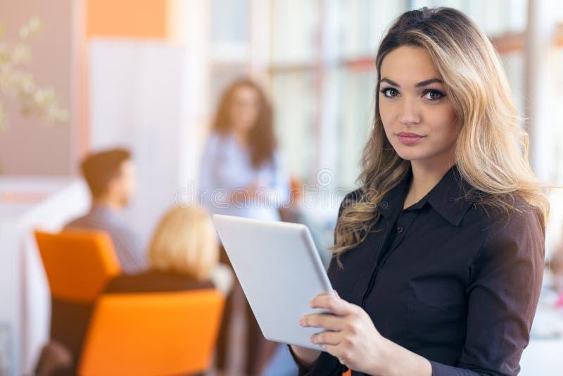 Portret van jonge bedrijfsvrouw bij modern startbureaubinnenland, team in vergadering op achtergrond royalty-vrije stock afbeelding