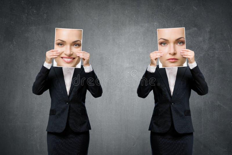Portret van jonge bedrijfsvrouw die haar stemming verbergen onder maskers stock foto