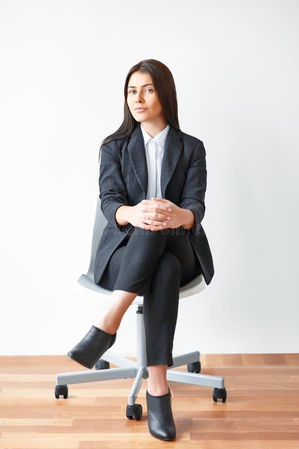 Portret van jonge bedrijfsvrouwenzitting op stoel royalty-vrije stock fotografie
