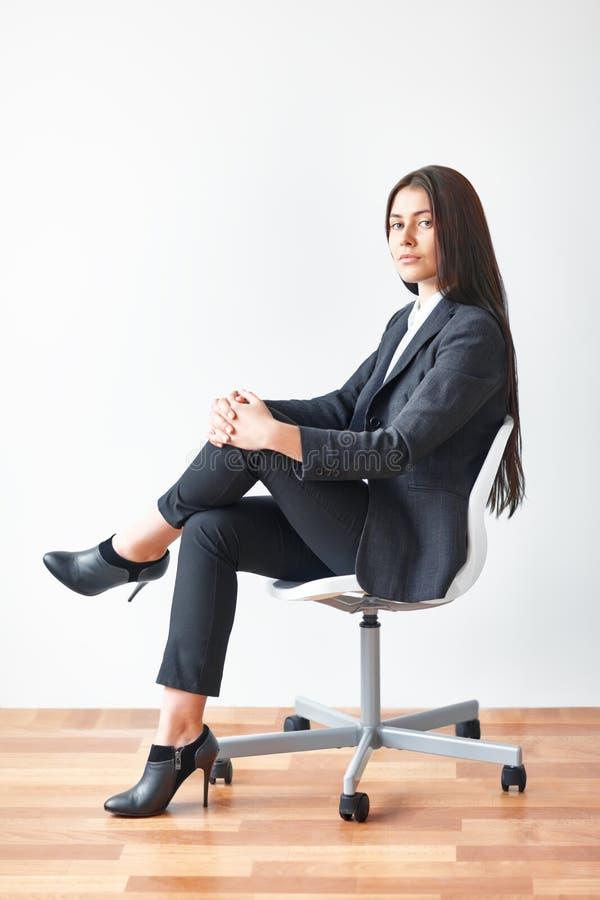 Portret van jonge bedrijfsvrouwenzitting op stoel stock foto