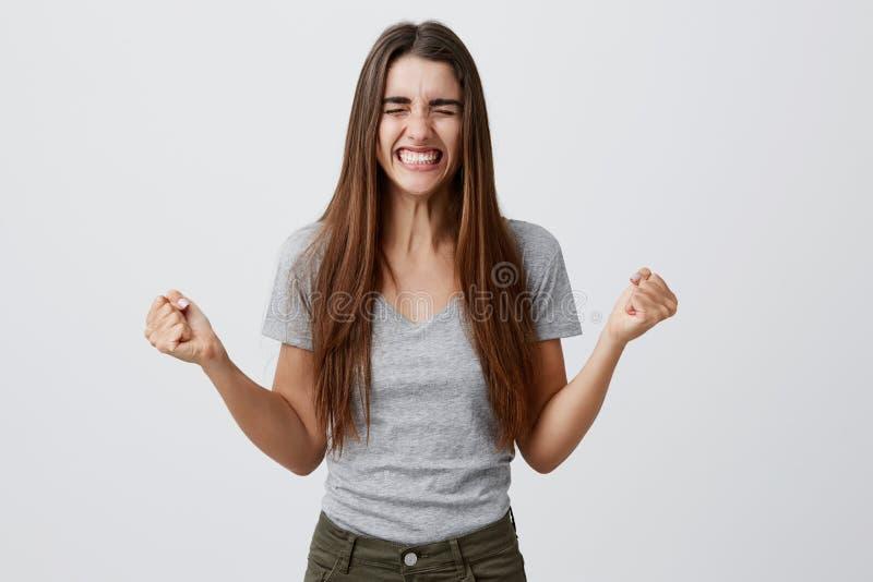 Portret van jonge blije gelukkige mooie vrouwelijke student die met lang donker haar in toevallige grijze uitrusting met tanden g stock foto's