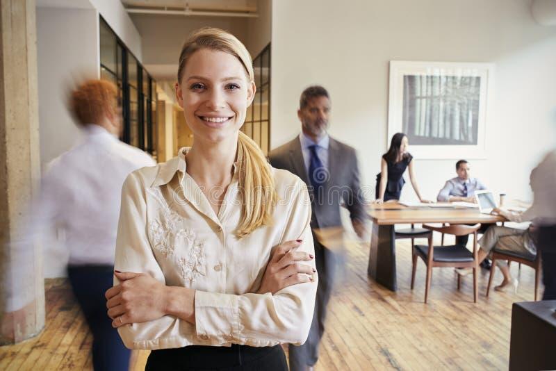 Portret van jonge blondevrouw in een bezige moderne werkplaats royalty-vrije stock foto's